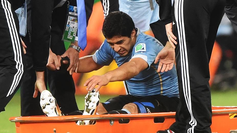 O uruguaio Luis Suárez é levado de maca para fora do campo para receber tratamento, após sofrer falta no jogo contra a Inglaterra no Itaquerão, em São Paulo