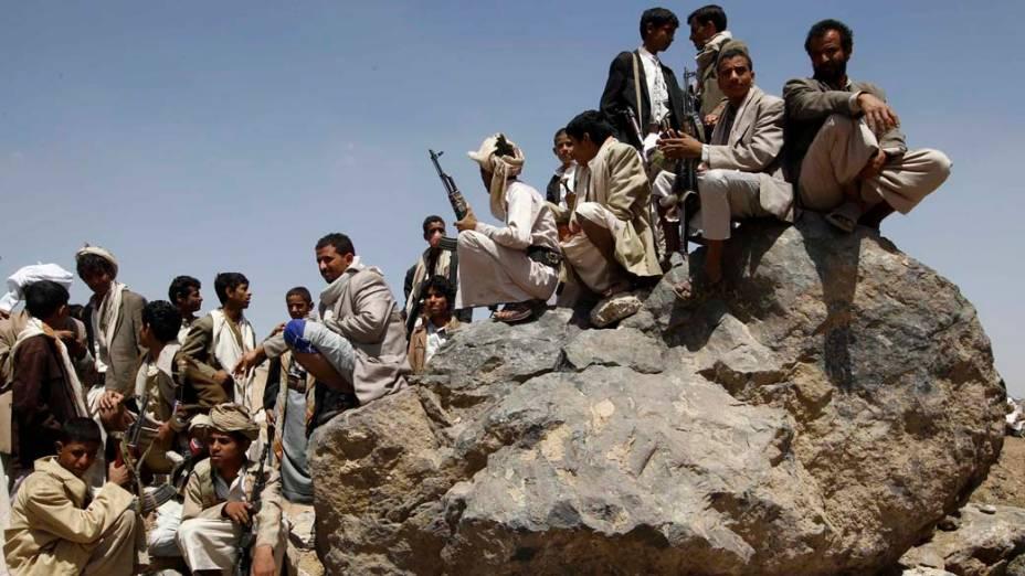 Combatentes tribais vigiam manifestantes anti-governo durante marcha próxima a praça Tahrir, em Sanaa, Iêmen