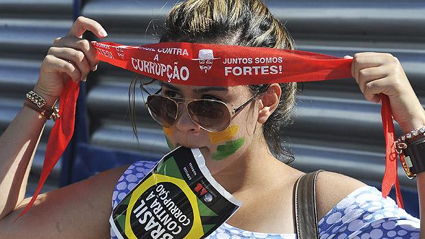 Jovem coloca faixa durante a marcha contra a corrupção na Esplanada dos Ministérios