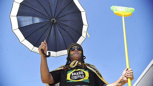 Manifestante com guarda-chuva e vassoura durante marcha contra a corrupção, na Esplanada dos Ministérios