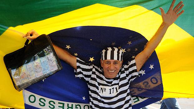 Participante embaixo da bandeira do Brasil, em marcha contra a corrupção, na Esplanada dos Ministérios