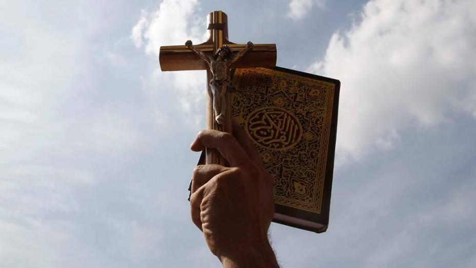 Egípcio carrega a cruz cristã com o Corão, durante manifestação a favor da tolerância religiosa, no centro do Cairo