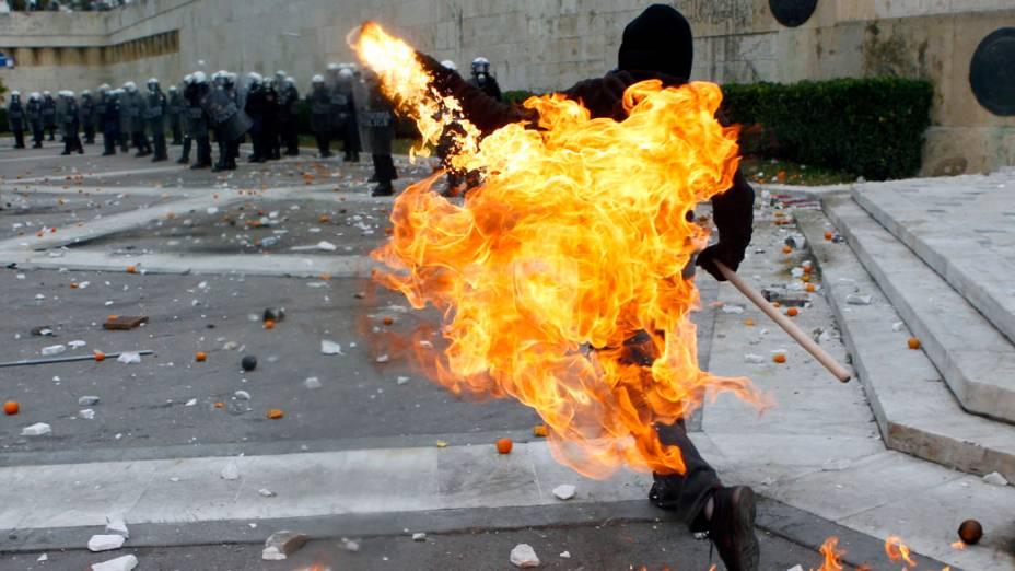 Manifestante arremessa bomba de petróleo contra políciais na praça Syntagma em Atenas, Grécia