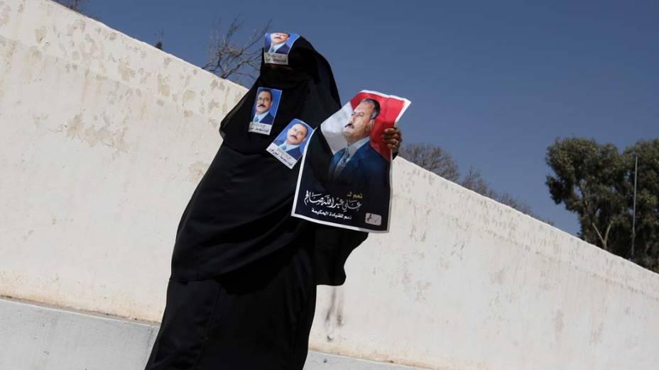Manifestante pró-governo com imagens do presidente Ali Abdullah Saleh durante manifestação no centro de Sanaa, Iêmen
