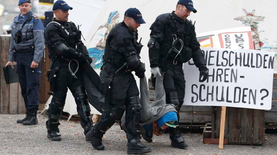 """Policiais carregam manifestante do """"Occupy Paradeplatz"""" em Zurique, na Suíça"""