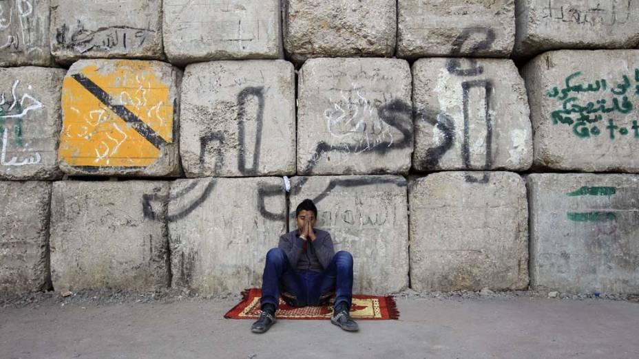"""Manifestante senta embaixo de muro com a mensagem """"livre"""" durante protesto contra o governo militar no Cairo, Egito"""