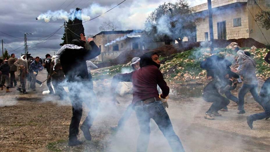 Manifestantes palestinos em meio a latas de gás lacrimogênio atiradas por soldados israelenses durante protesto contra o assentamento judaico de Cadonmen na Cisjordânia