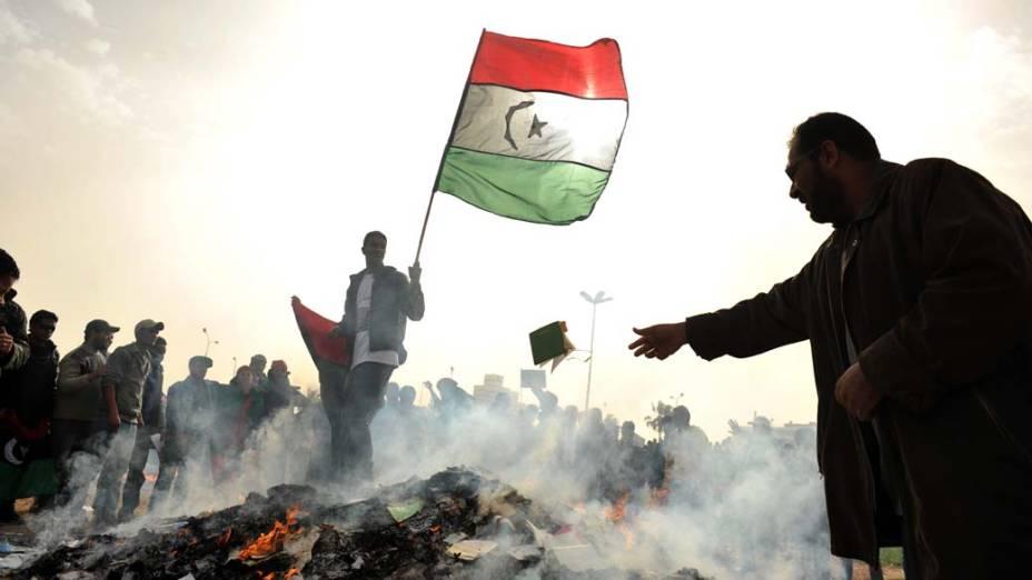 "Manifestante líbio queima o ""Livro Verde"", escrito pelo ditador Muamar Kadafi, durante protesto na cidade de Benghazi"