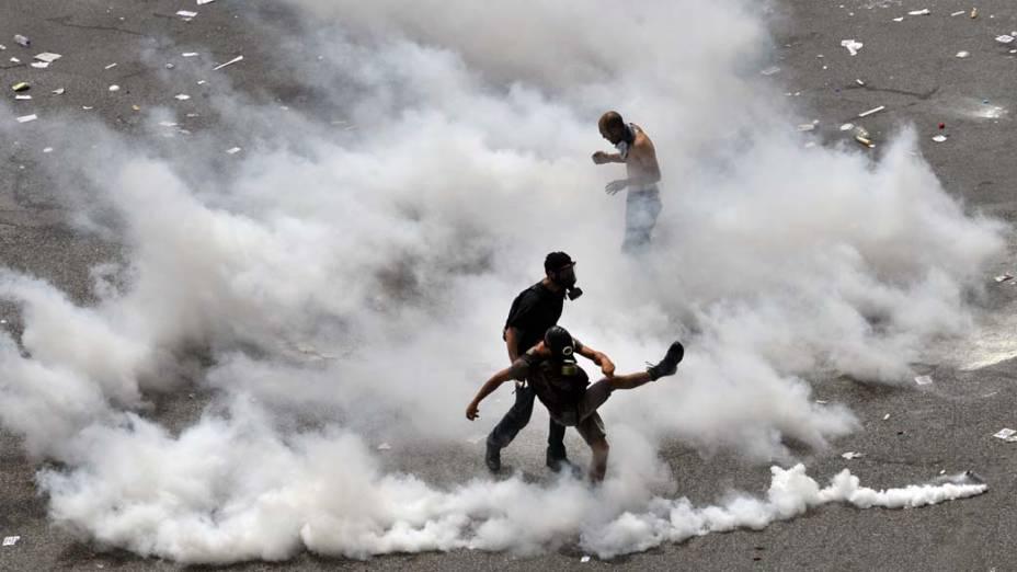 Manifestantes em conflito com a polícia durante protesto em Atenas, Grécia. Os manifestantes pedem a derrubada de um pacote de medidas de austeridade, que deve aumentar os impostos e privatizações no país
