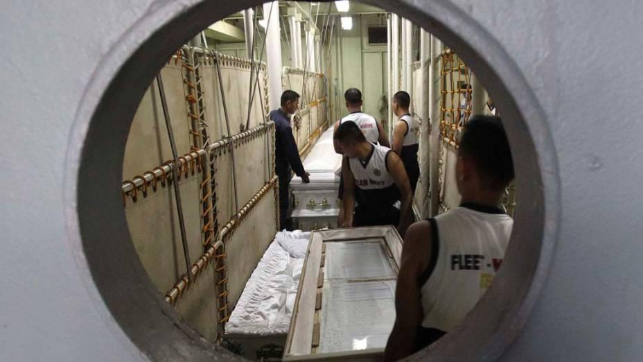 Membros da marinha carregam caixões que serão utilizados para enterrar as vítimas do tufão que atingiu as Filipinas nesse final de semana