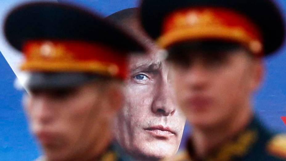 """Em São Petersburgo, marinheiros russos em frente a um pôster da campanha """"All-Russian Peoples Front"""", liderada pelo primeiro-ministro Vladimir Putin"""