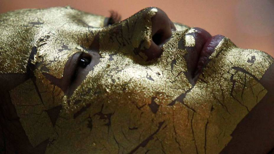 Cliente durante tratamento facial com folhas de ouro 24K que diz-se deixar a pele mais branca em Hanói, Vietnã