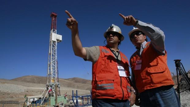 Rene Aguilar, chefe de operações do resgate (à esquerda) e Walter Veliz, responsável pela perfuradora conversam à frente da mina onde estão presos os 33 mineiros