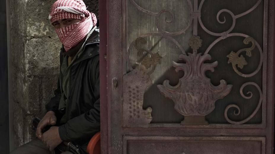 Membro do Exército da Síria Livre guarda portão durante funeral em Qusayr, Síria