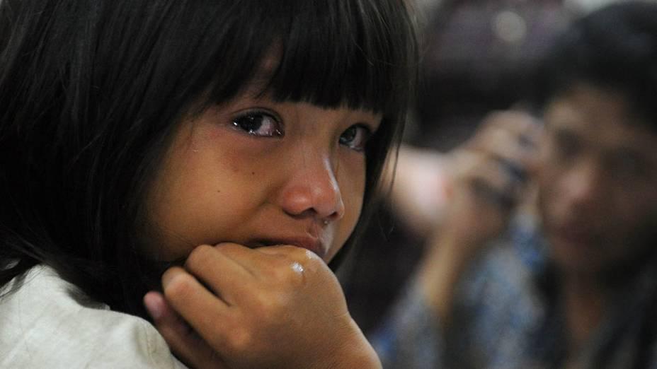 Criança chora e espera informações do avião que desapareceu na quarta-feira (9) com 46 passageiros. Equipes de resgate procuram sobreviventes
