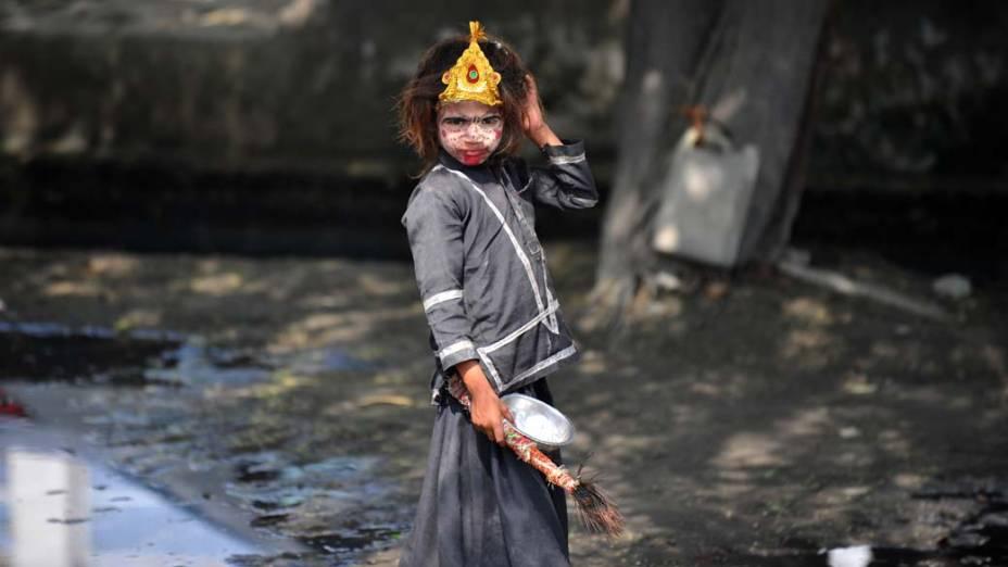 Menina de rua com o rosto pintado em Noida, periferia de Nova Délhi, Índia