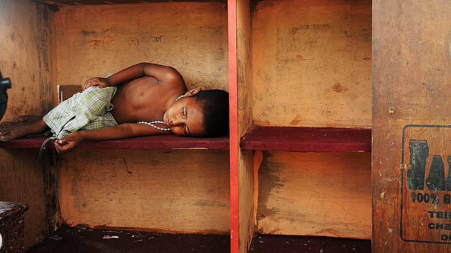 Criança dorme na rua perto de uma barraca para escapar do forte calor que atinge a cidade de Calcutá, na Índia