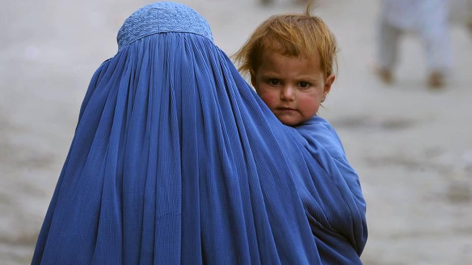 Mulher afegã carrega seu filho na parte velha de Cabul. O país devastado pela guerra ainda enfrenta pobreza, desemprego e falta de infra-estrutura