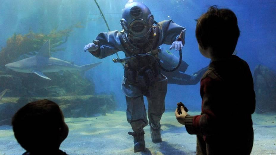 Crianças assistem a uma apresentação de mergulhadores em trajes antigos no aquário de Melbourne, na Austrália