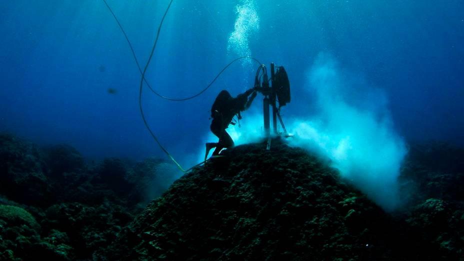 Mergulhador do Instituto de Ciência Marinha Australiana examina corais