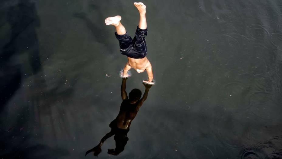 Menino mergulha no rio Dambovita em Bucareste, na Romênia. As temperaturas bateram os 36°C no local, matando cinco pessoas