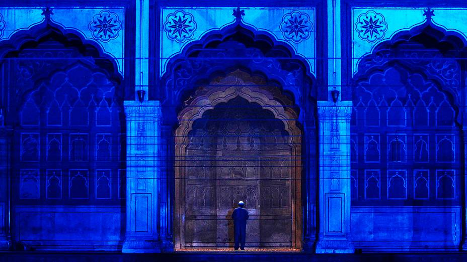 Muçulmano reza dentro da Jama Masjid (Grande Mesquita), iluminada por uma luz azul. A luz faz parte da campanha de prevenção ao diabetes