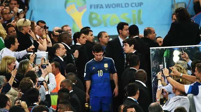 Lionel Messi pega o troféu de melhor jogador da Copa de cabeça baixa, após perder da Alemanha na final da Copa no Maracanã, no Rio