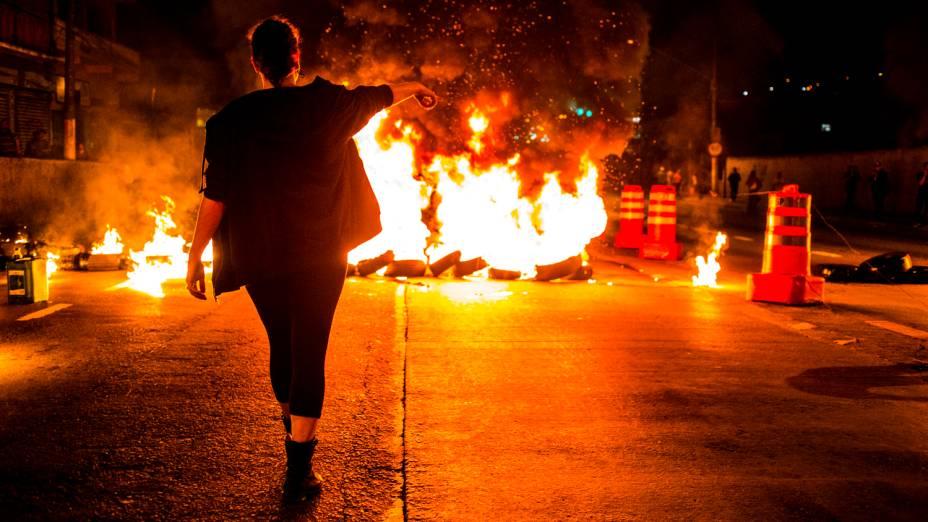 Manifestante interdita a Avenida MBoi Mirim durante protesto organizado pelo Movimento Passe Livre (MPL) contra o corte de linhas e pela duplicação da MBoi Mirim no Largo do Piraporinha, nesta segunda-feira (21), em São Paulo