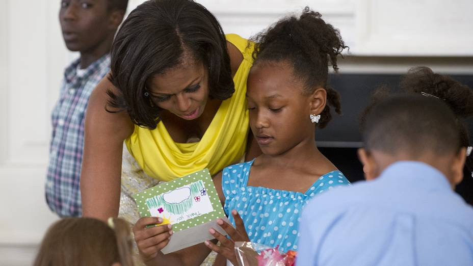Michelle Obama lê um cartão de Dia das Mães com crianças de famílias de militares, enquanto eles criam cartões e outros artesanatos na State Dining Room, na Casa Branca, em Washington