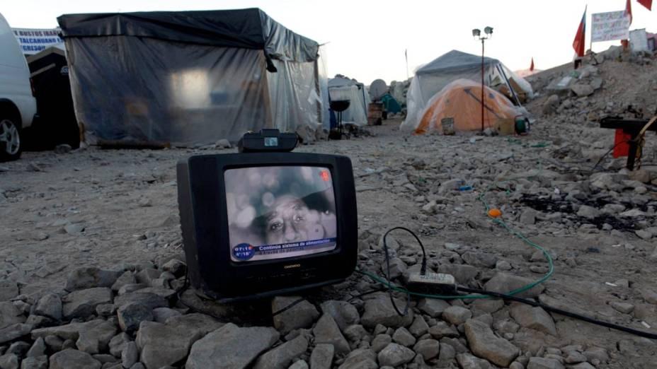 Em acampamento onde familiares esperam por notícias dos mineiros, televisão mostra a imagem dos trabalhadores presos na mina que desmoronou em San José, Chile
