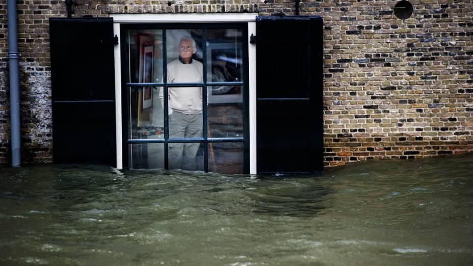 Morador olha o nível da água através de sua janela em Dordrecht, Alemanha