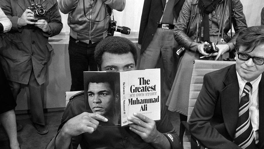 Muhammad Ali com uma cópia de sua autobiografia no aeroporto de Frankfurt, em outubro de 1975. Ele foi à cidade alemã para lançar o livro na maior feira literária do mundo