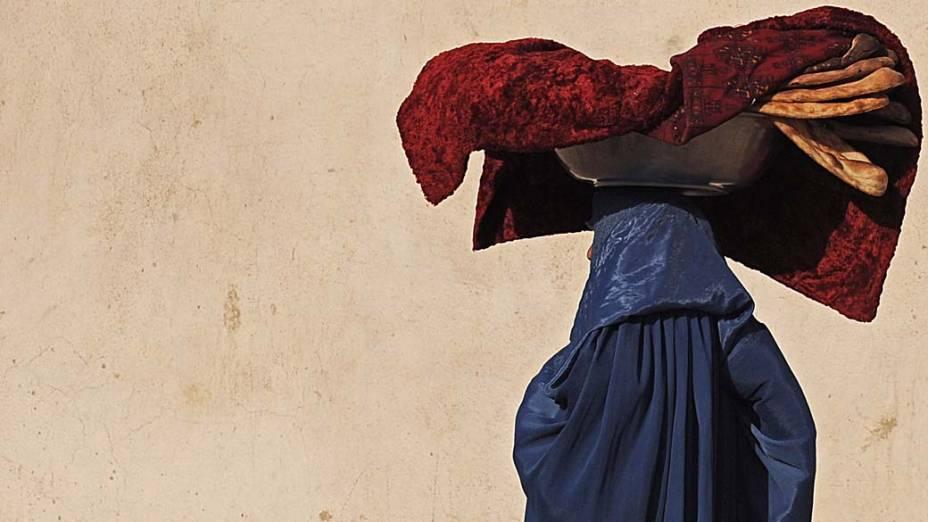 Mulher carrega pães nas ruas de Cabul, no Afeganistão