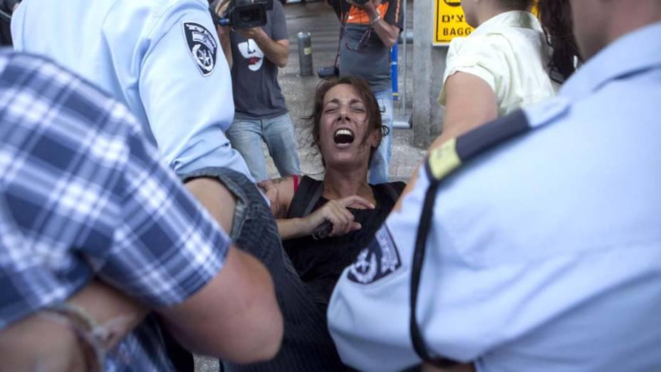 Policiais israelenses prendem uma ativista no aeroporto internacional David Ben Gurion, perto de Tel Aviv. Manifestantes se reuniram para receber ativistas que visitariam a Cisjordânia e outros territórios palestinos