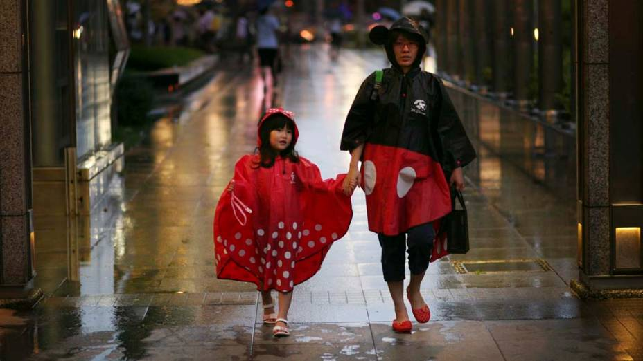 Mulher caminha com sua filha em dia chuvoso na cidade de Taipei, Taiwan