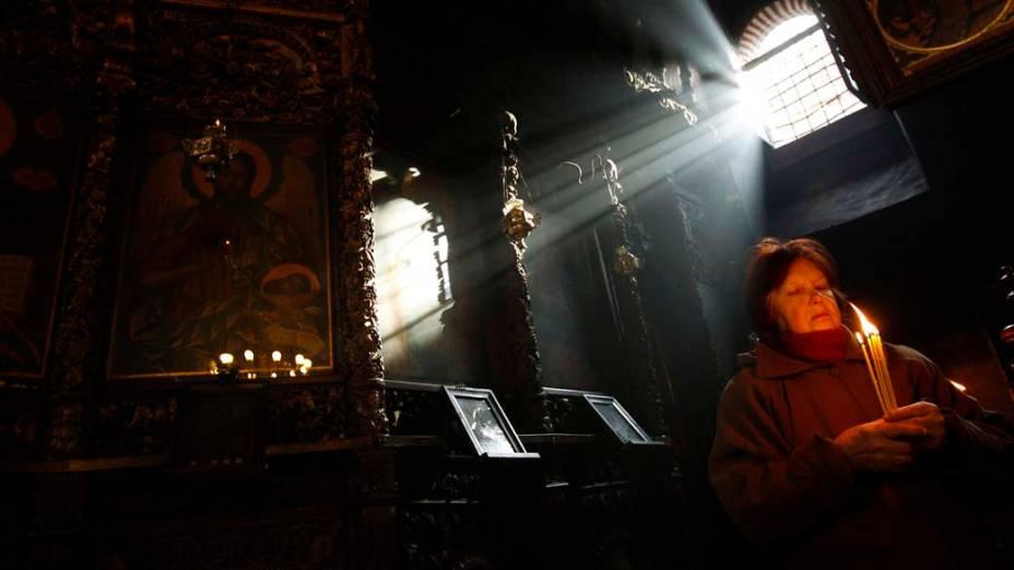 Mulher reza em igreja na cidade de Blagoevgrad, Bulgária