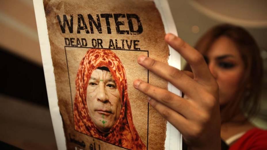 Em Trípoli, mulher com o jornal Arus al-Bahr, com imagem de Kadafi vestido com traje tradicional feminino