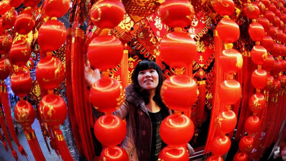 Chinesa escolhe lanternas em mercado preparado para vendas das celebrações de Ano Novo em Yiwu, China