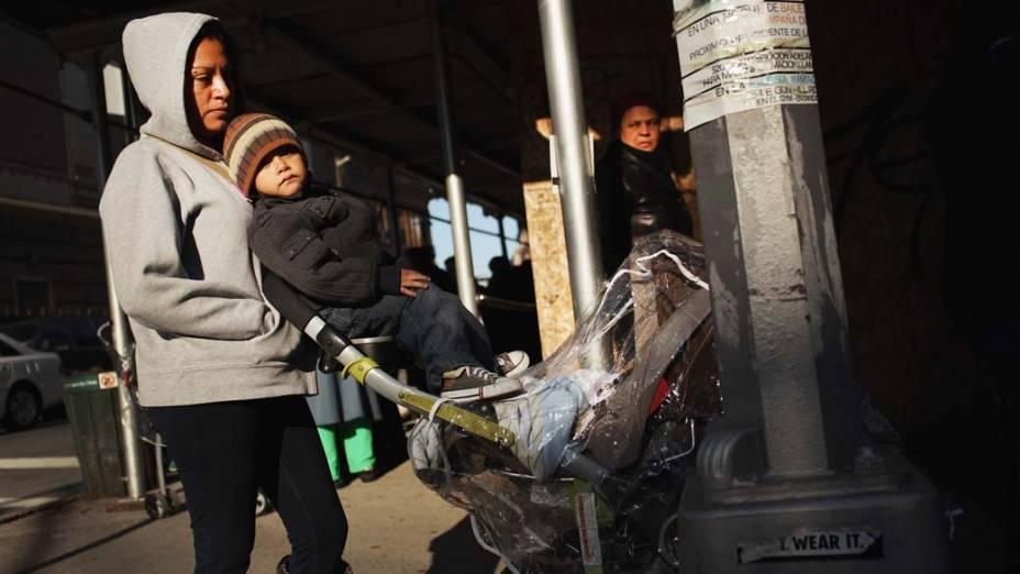 Família aguarda para receber leite em programa governamental em Nova York