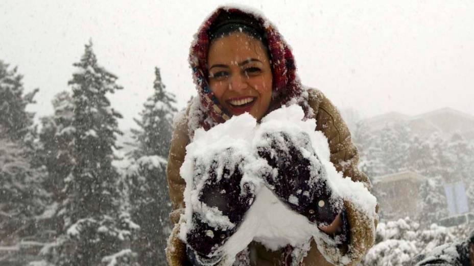No Irã, mulher recolhe neve durante nevasca