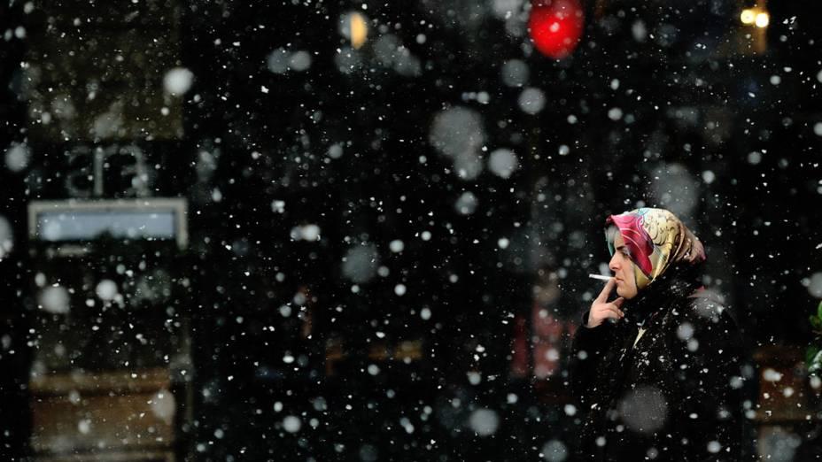 Mulher caminha sob a neve por avenida de Istambul, Turquia