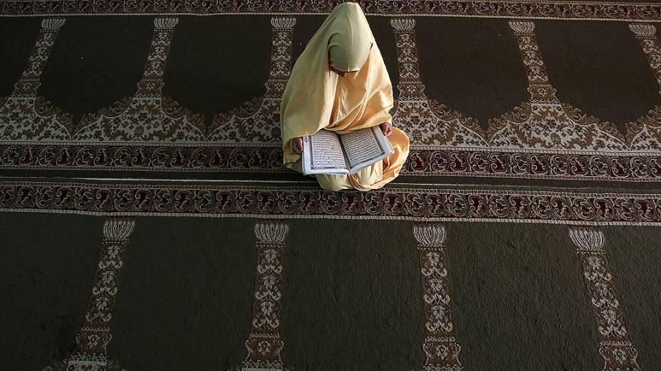 Menina palestina lê versos do Alcorão o livro sagrado do Islã, em um acampamento na Cidade de Gaza