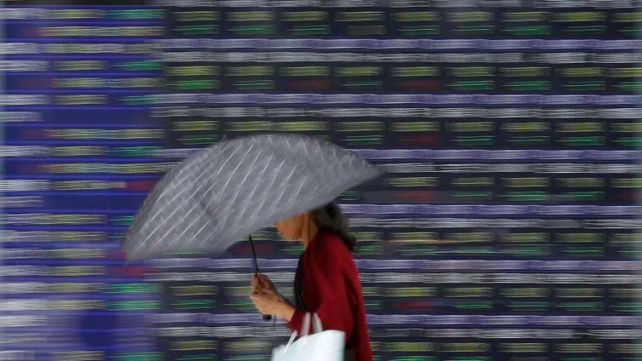 Mulher passa por painel de cotações em frente a Bolsa de Valores de Tóquio, Japão