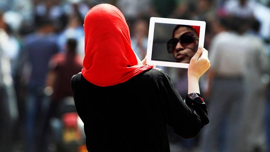 Mulher egípcia usa o seu tablet durante manifestação no marco do Cairo Tahrir Square