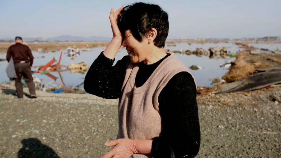 Três dias após o forte terremoto e tsunami que atingiram a costa nordeste do Japão, mulher não encontra vestígios de sua casa na cidade de Soma, Fukushima