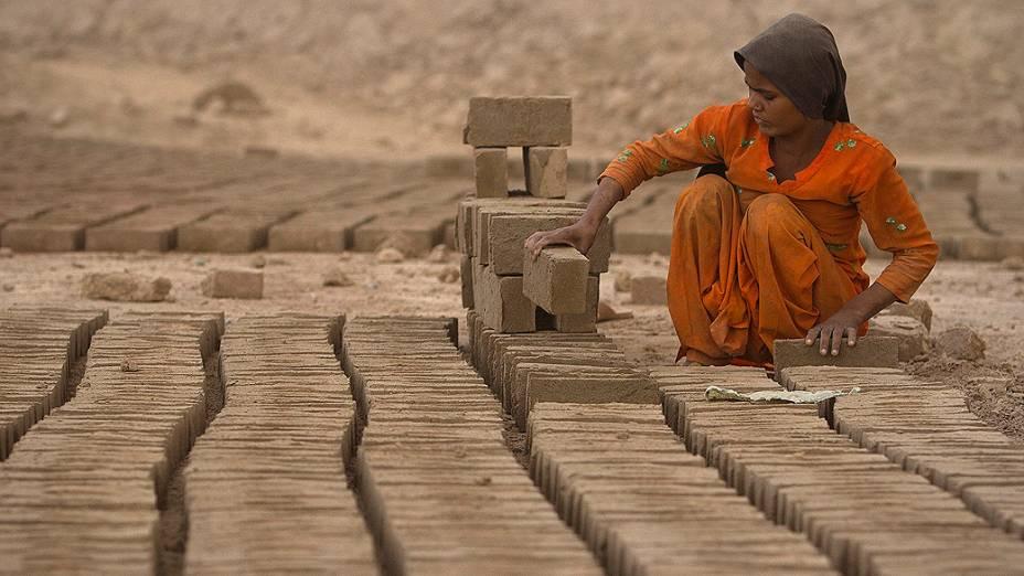 Menina arruma tijolos para ser cozidos em um forno de fábrica ao ar livre nos arredores de Islamabad