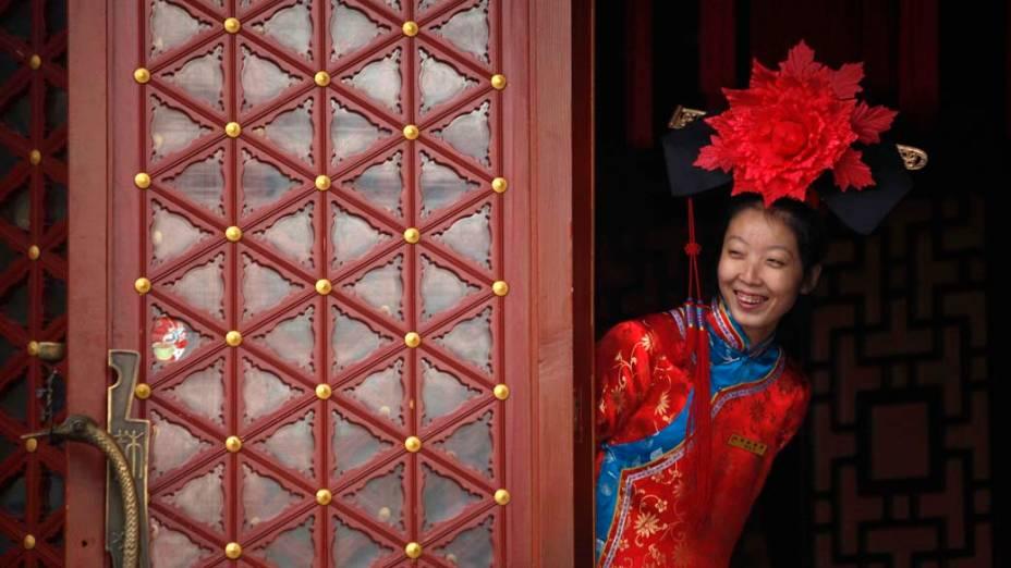 Garçonete vestida com roupas tradicionais da dinastia Qing em restaurante em Pequim, China