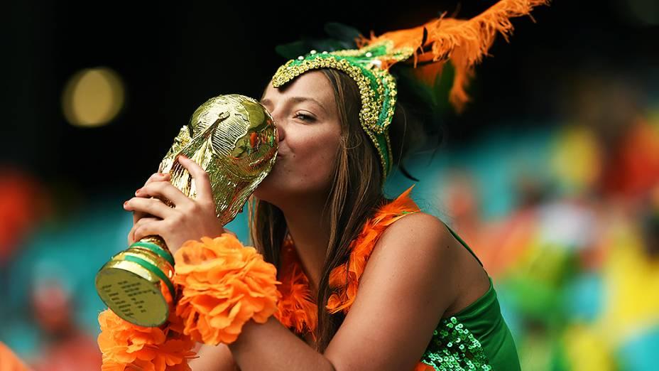 Torcedora beija réplica da taça na partida entre Holanda e Costa Rica na Arena Fonte Nova, em Salvador