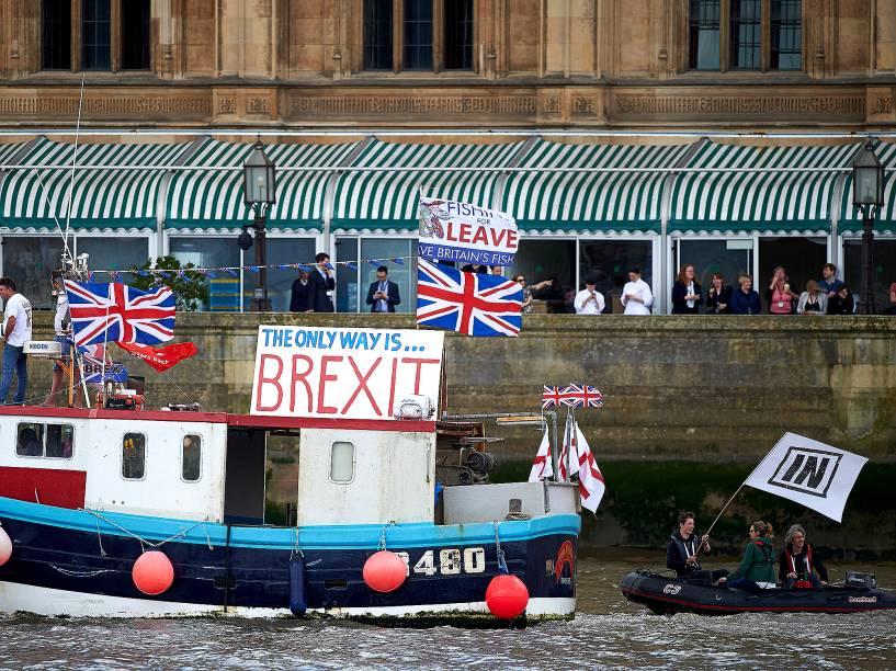 Barco com bandeiras contra a permanência do Reino Unido na União Europeia, é seguido por um bote com uma bandeira à favor, em Londres