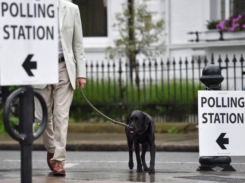 Homem chega para votar o referendo com seu cachorro, em Londres